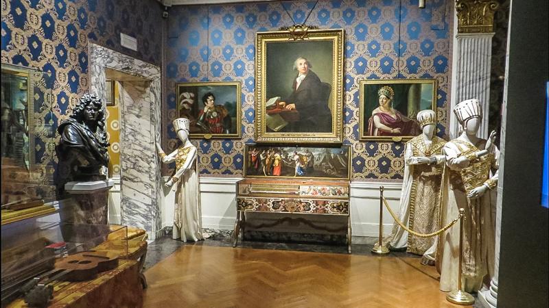 In questa sala del museo teatrale alla scala ci sono quattro abiti di scena sfarzosi in oro, tre autoritratti, un pianoforte dettagliato in fiori e affrescato sulla chiusura e sulla sinistra un violino.