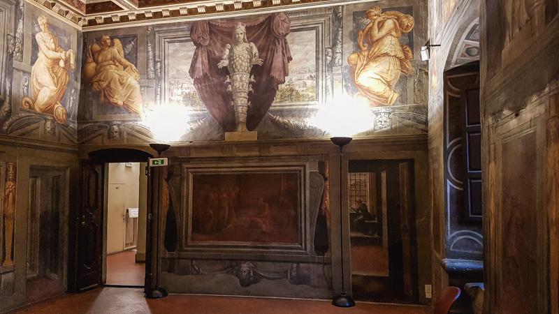 La bellissima sala del trionfo della virtù di Casa Vasari ad Arezzo. Spiccano in primo piano gli affreschi decorativi sopra le porte di ingresso dell'ambiente successivo e gli affreschi laterali