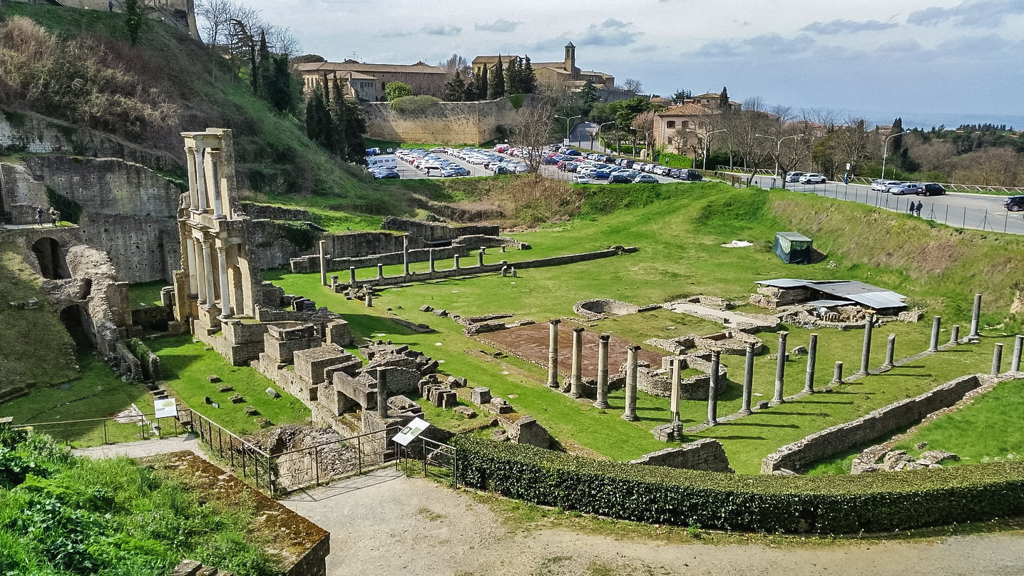 L'antico anfiteatro romano di volterra visto al completo con in primo piano le colonne rimaste in piedi e parte del frontescena. Tutto inserito in un prato verde.