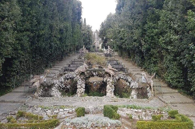 Una scalinata dentro il parco di Villa Garzoni a Collodi, nel mezzo di verdi alberi altissimi che le fanno quasi da fortificazione. Nel mezzo della scalinata ci sono sculture in pietra e bellissime nicchie.