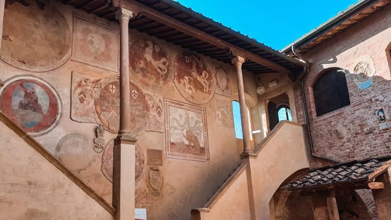 Una scalinata interna del Palazzo Pretorio di Certaldo che porta alle stanze del piano superiore. Spiccano sul muro i vari affreschi colorati con i simboli delle famiglie più importanti.
