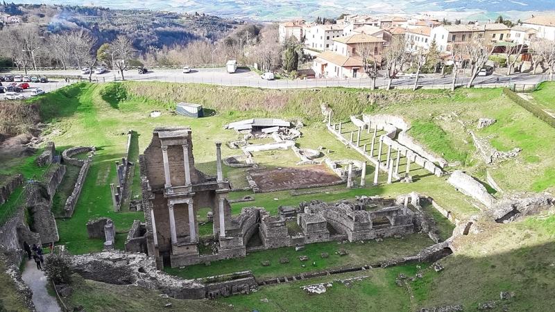 I ruderi dell'anfiteatro romano di Volterra con in primo piano ciò che rimane del frontescena e del palco. Sullo sfondo una strada che porta verso la valle su cui si trova Volterra.