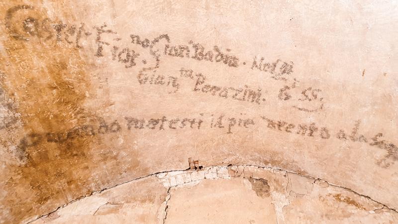Un muro scarno del carcere civile del Palazzo pretorio di Certaldo su cui ci sono delle scritte nere fatte da uno dei prigionieri