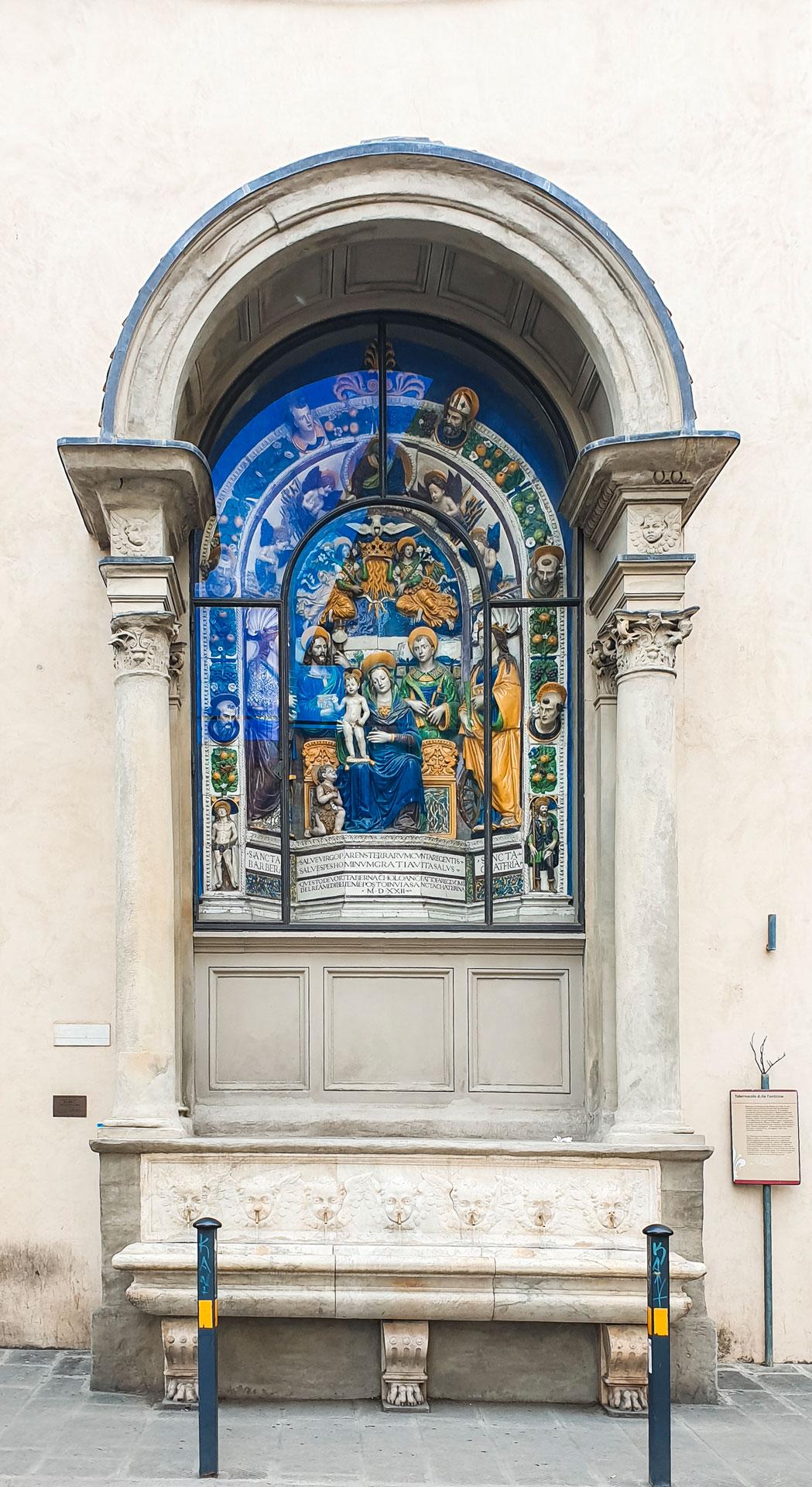 Il bellissimo tabernacolo delle fonticine con la pala centrale colorata principalmente in blu e giallo e verde. Sotto una fontana con vasca con le teste dei putti che gettano l'acqua.