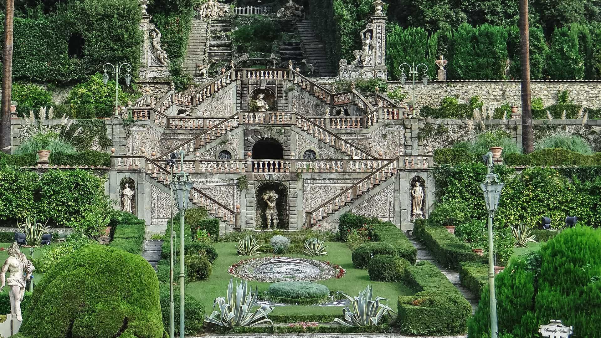 Le due rampe di scale con i tre pianerottoli che portano alla villa garzoni di collodi. In ogni piano c'è una statua centrale e due laterali. In primo piano poi parte del disegno formato con i cespugli del giardino.