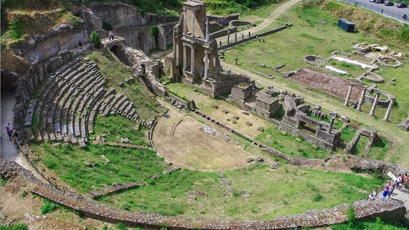 Un primo piano sul frontescena e sulle gradinate per gli spettatori dell'antico anfiteatro romano di Volterra. Si nota ancora la forma ellittica della cavea e alcuni gradoni ancora rimasti in piedi.