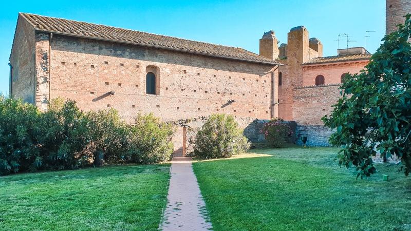 Un piccolo giardino esterno al palazzo pretorio di certaldo sul cui fondo si vede una struttura in mattoni con una grande finestra centrale.