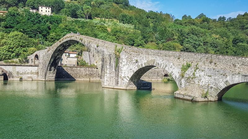 Il ponte del diavolo in Toscana visto nella sua interezza e nella sua forma particolare. L'arco centrale rispetto agli altri è molto più rialzato come a formare una punta. Sotto l'acqua limpida del fiume che scorre.
