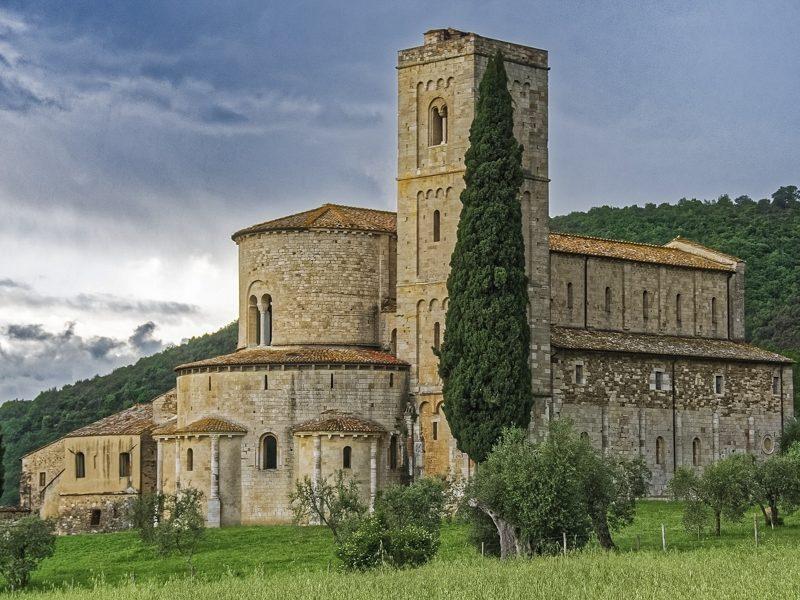 Una vista sulla bellissima Abbazia di Sant'Antimo nel pieno della Val d'Orcia. La chiesa è costruita tutta in mattoni e presenta un campanile a forma rettangolare. Si trova immersa nel verde della valle.