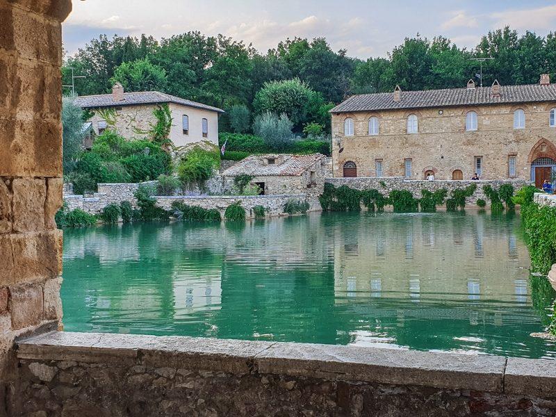 La grande vasca termale di Bagno Vignoni nel mezzo della piazza principale del piccolo paese. Sullo sfondo si intravedono gli alberi verdi che circondano il paese e un edificio in mattoni.