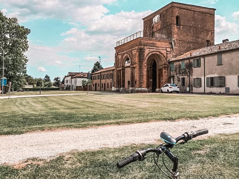 La delizia estense di belinguardo con la sua entrata monumentale composto da un grande e altissimo arco sormontato da una terrazza. In primo piano un verde prato con alcuni alberelli.