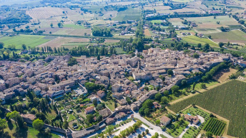 La vista dall'alto di Bevagna, il borgo medievale umbro. Si può notare la sua forma a fortezza con le tante case medievali tutte incorporate al centro. Intorno il verde delle coltivazioni e dei colli.