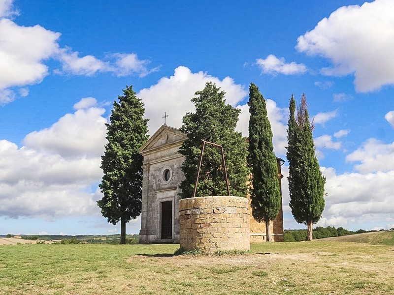 La bellissima e suggestiva cappella della madonna di vitaleta in posizione solitaria su un altura della val d'orcia. La cappella ha accanto a se alcuni pini e davanti un piccolo pozzo.