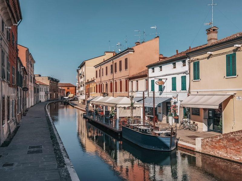 Il bellissimo borgo di Comacchio in provincia di Ferrara con i suoi piccoli canali e le barchette ormeggiate. Ai lati la passeggiata con i locali tipici e le abitazioni colorate.