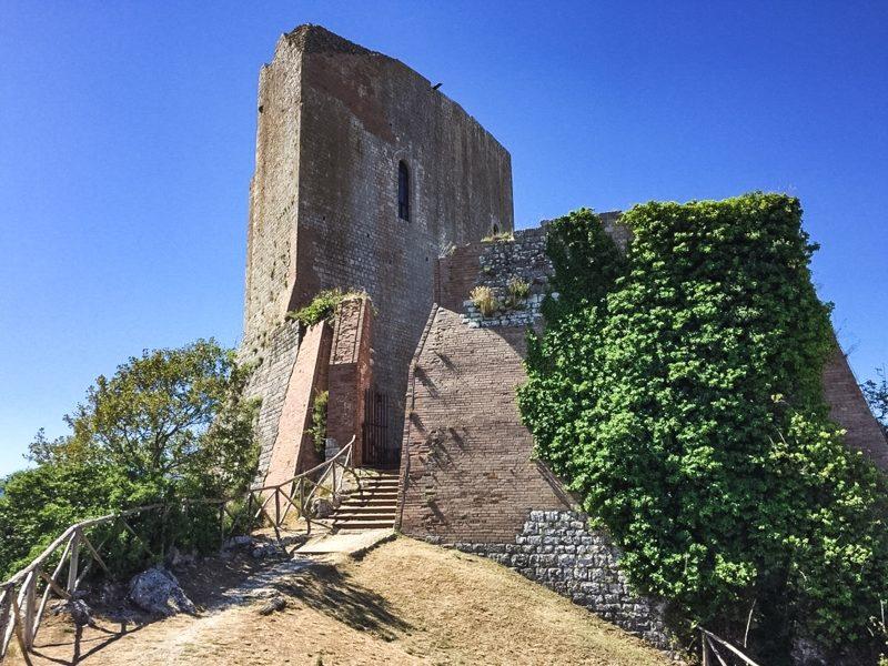 Ciò che rimane dell'antica Rocca a Tentennano a Rocca d'Orcia. Un alto torrione medievale con accanto ruderi della vecchia fortificazione che sono catturati della verde vegetazione.
