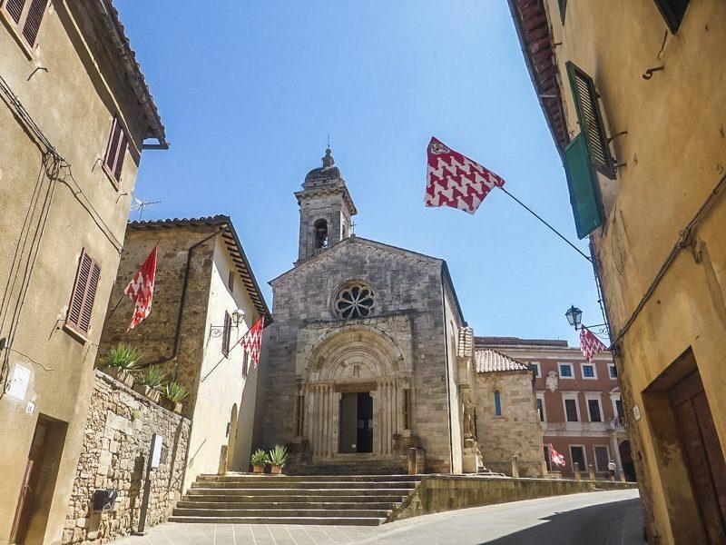 Uno sguardo su una delle piazzette più importanti di San Quirico d'Orcia con in primo piano la facciata della chiesa della Madonna di Vitaleta. Negli edifici vicino ci sono le bandiere del quartiere appese.