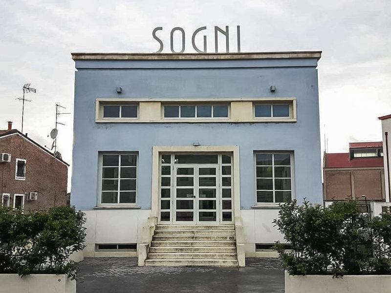 Tresigallo è una destinazione della provincia di ferrara che si distingue dalle altre. Gli edifici sembrano usciti da un set cinematografico e qui ne vedi un esempio. Una struttura quadrata blu con scritto sogni in cima al soffitto.