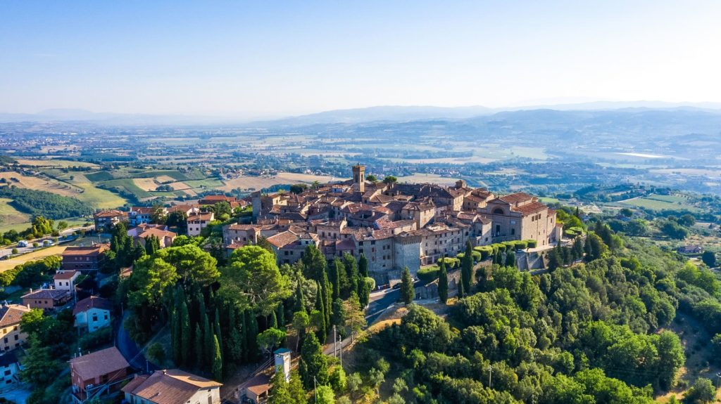 Monte Castello di Vibio vista dall'alto e da lontano. Il paese è arroccato sopra un monte, dal quale si può avere una vista completa su tutta la verde valle circostante.