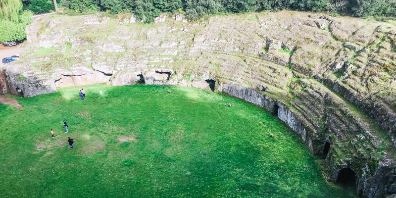 La vista dall'alto dei ruderi dell'antico anfiteatro romano contenuto all'interno del parco archeologico di Sutri. Si vedono ancora i gradoni su cui si sedeva il pubblico e le porte di accesso.