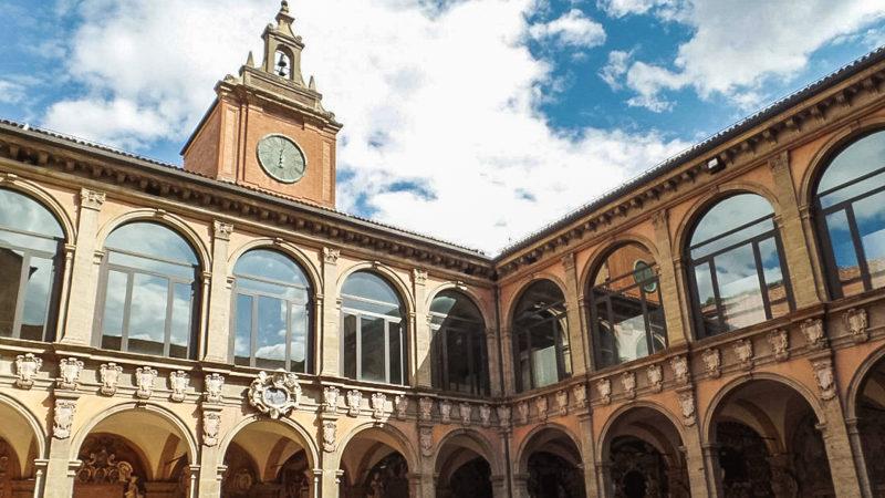 Il cortile interno dell'archiginnasio di bologna con i vari finestroni in vetro al secondo piano e le varie logge arcate al pian terreno. Nel mezzo spicca verso il cielo la piccola torre con orologio.