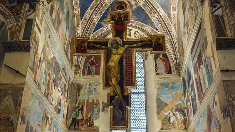 La croce centrale e gli affreschi colorati che adornano la zona dell'altare della basilica di san francesco. Una delle cose in assoluto che devi vedere ad arezzo in un giorno.