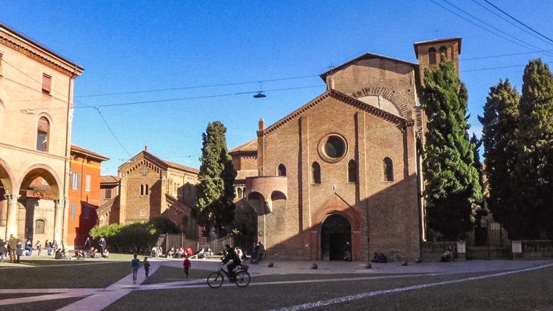 La bellissima piazza di santo stefano a bologna è una delle mete da vedere in città in un giorno. Sullo sfondo si vede la facciata della basilica di santo stefano con accanto quattro altissimi alberi.