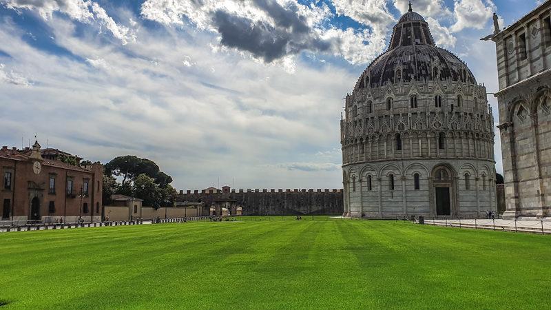 Il battistero di pisa si trova nella piazza dei miracoli vicino all'ingresso fortificato. Accanto al battistero un lungo prato verde rende tutto più elegante e invitante per il turista che visita Pisa.