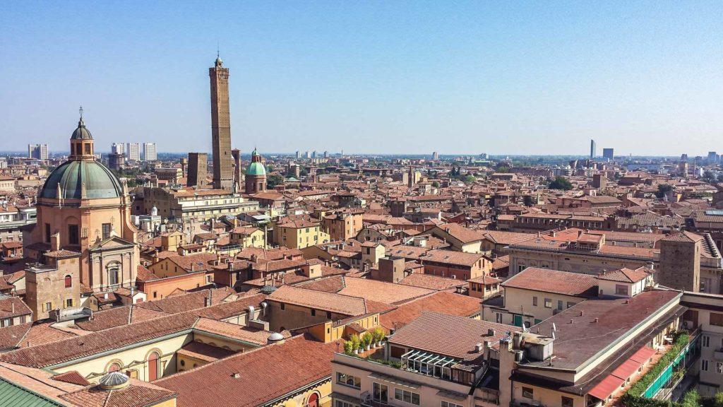 Una vista spettacolare dall'alto su tutta la città di Bologna. Tra i tanti edifici spiccano la cupola di una chiesa e soprattutto l'altissima torre degli asinelli. Sullo sfondo gli edifici moderni della città.
