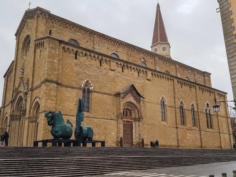 L'imponente esterno della cattedrale di arezzo con la sua entrata monumentale sormontata da un tabernacolo e colonnato. Spicca sullo sfondo il campanile a punta della chiesa.