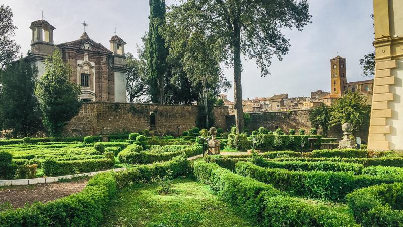 Il bellissimo giardino esterno di Villa Savorelli contenuto nel parco archeologico di Sutri. I verdi e bassi cespugli addobbano l'esterno come se fosse un piccolo labirinto, con al centro un alto albero.