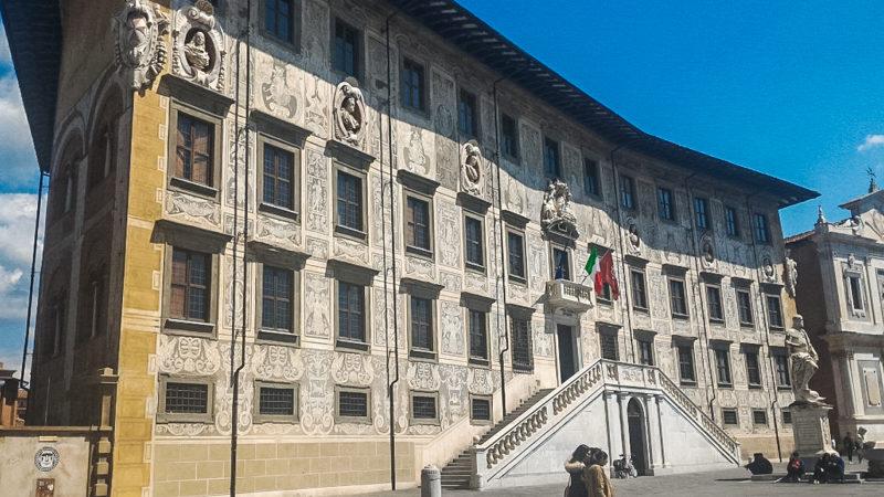 Piazza dei cavalieri a pisa ha tantissimi edifici molto particolari e importanti. Uno di questi è il palazzo della carovana che erge maestoso con il suo ingresso sopra a due rampe di scale e i tanti fregi sulla facciata.