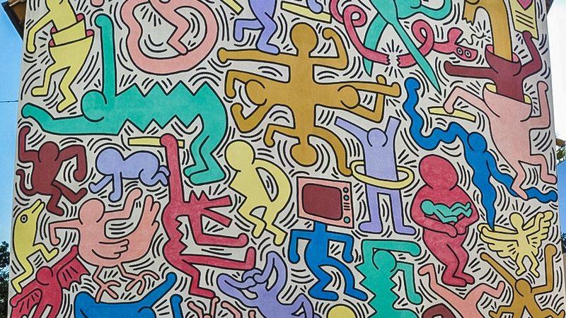 Il murale di keith haringn addobba completamente la facciata dell'edificio senza lasciare alcun spazio. I colori utilizzati sono colori molto caldi come l'azzurro, il giallo e il rosso e rappresentano figure di persone e animali.