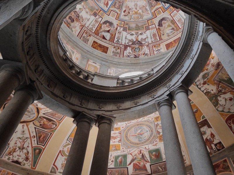 Una serie di affreschi colorati che abbelliscono la zona delle scalinate che portano al piano superiore del Palazzo Caprarola. In primo piano le colonne e gli archi delle scale a forma ellittica.