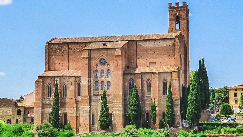 La bellissima basilica di san domenico è adagiata su uno sperone roccioso con alcuni alberi che fanno da contorno. La basilica è una delle cose da vedere in un giorno se siete a siena perché è meravigliosa!