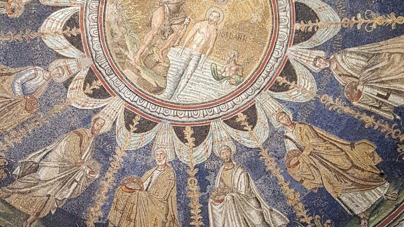 Un primo piano sul mosaico centrale del battistero neoniano. Al centro in colore dorato c'è il battesimo di gesù mentre sotto sono rappresentati gli apostoli con sfondo in mattonelle blu.
