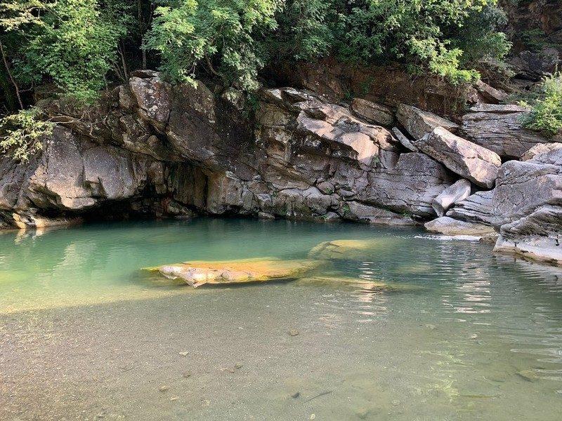 Una grandissima polla d'acqua limpida di colore azzurro verdastro con sullo sfondo dei grandi massi e una piccola grotta. In primo piano la sabbia del fondo dell'acqua.