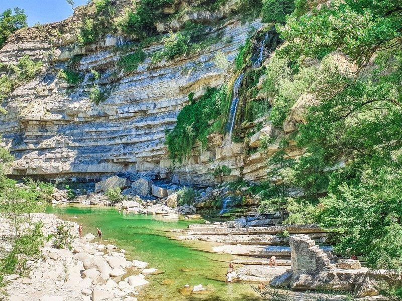 Una zona paradisiaca con un fiumiciattolo di acqua limpida che scorre in un dirupo nel mezzo dei sassi e una cascata altissima che scende dall'alto facendosi spazio tra la vegetazione.