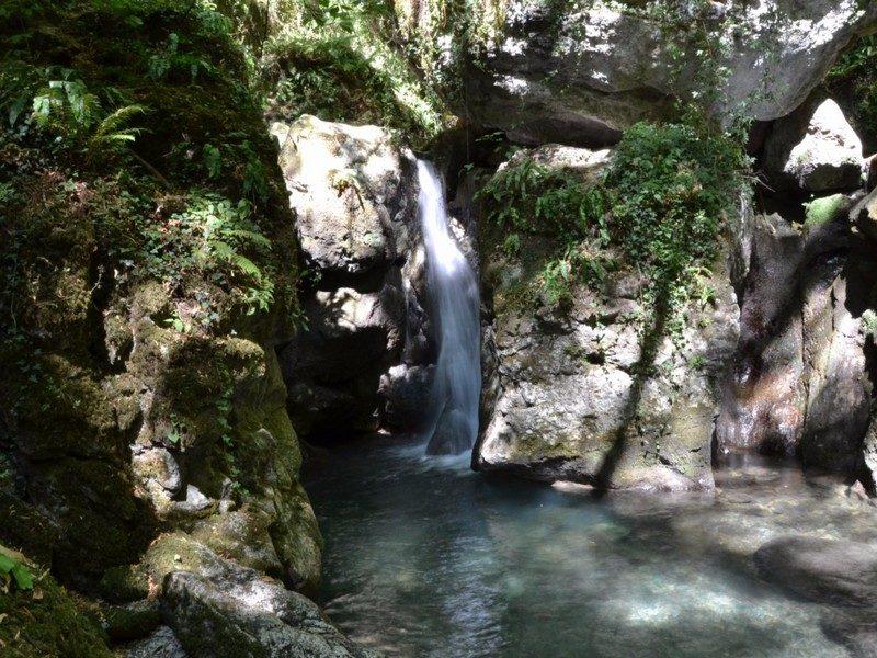 Tra le riserve naturali in toscana c'è le cascate di Candalla, un luogo paradisiaco. Sullo sfondo si vede una cascatella di acqua fredda nel mezzo delle rocce e della vegetazione che si butta su una polla di acqua limpida.