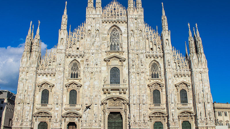 Un primo piano sulla bellissima facciata del Duomo di Milano su cui spiccano le altissime guglie e le tante finestre e grandi porte d'ingresso.