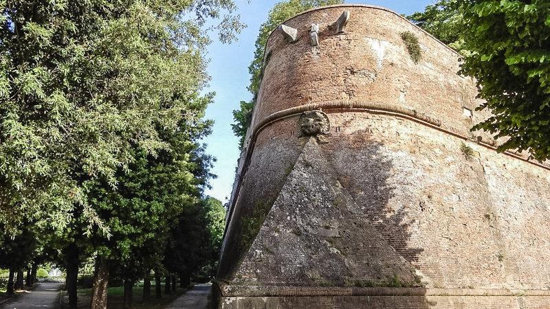 In questa foto si può vedere uno dei profondi bastioni angolari della fortezza di santa barbara a siena. Il tutto inserito in un bellissimo giardino con verdi alberi e camminamenti all'ombra.