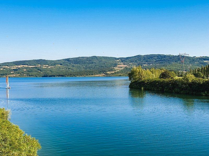 Un grande bacino d'acqua azzurra contornato da verdi colli e alberi altissimi. Sullo sfondo una barchetta che naviga tranquilla nell'acqua del Lago del Bilancino.