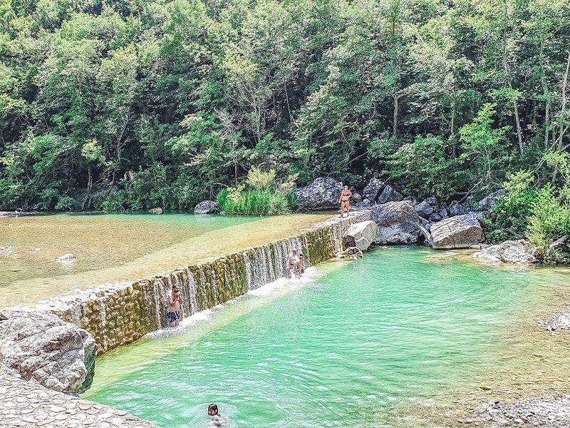 Una piscina d'acqua limpida che si forma grazie ad una larga ma bassa cascata che fa anche da idromassaggio. La piscina si trova dentro una riserva naturale in toscana con i suoi verdi e alti alberi.