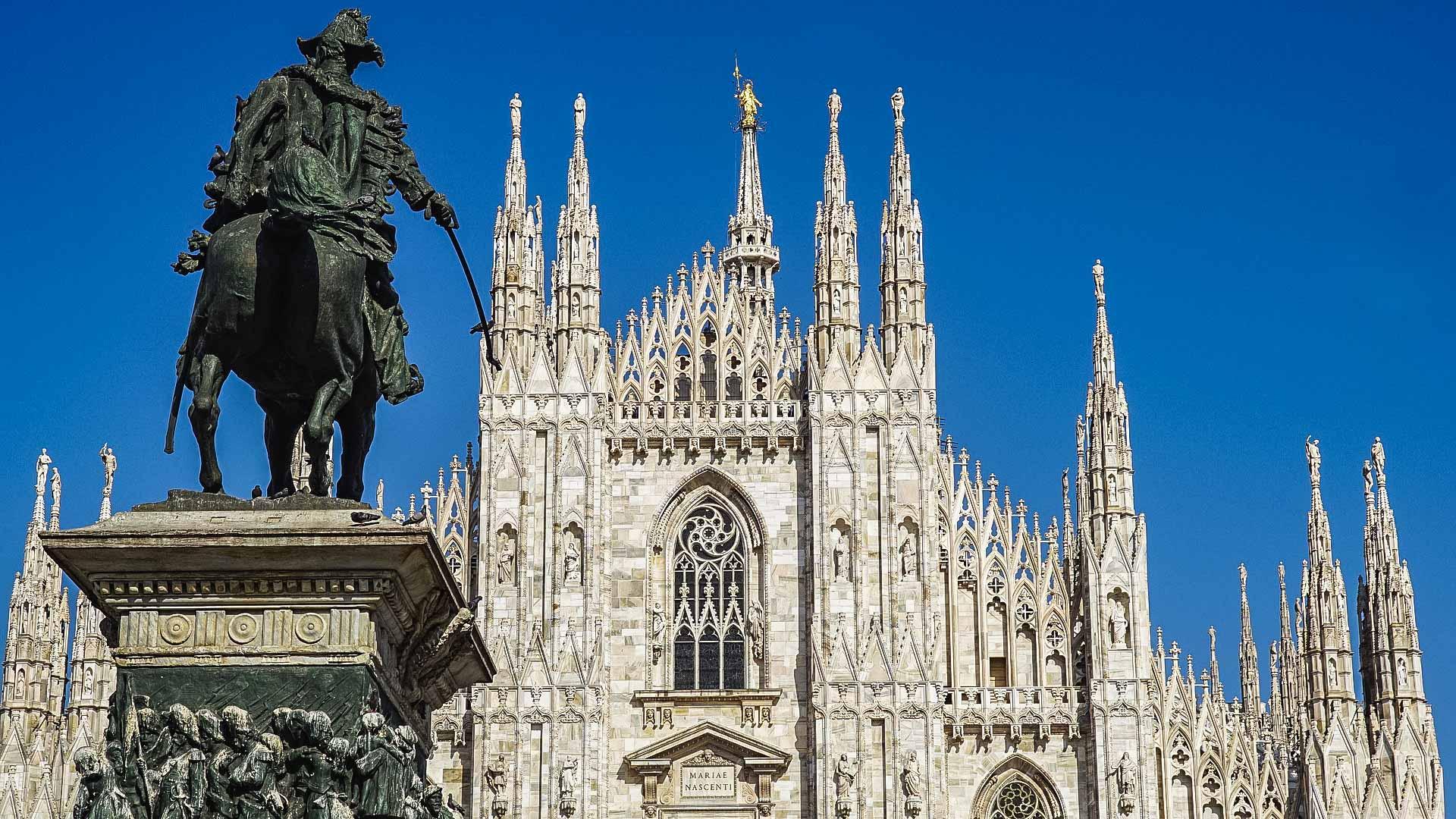 Una visione parziale sulla bellissima facciata del Duomo di Milano con le sue altissime guglie. Sulla destra spicca in primo piano la statua di Vittorio Emanuele che indica con la spada il Duomo.