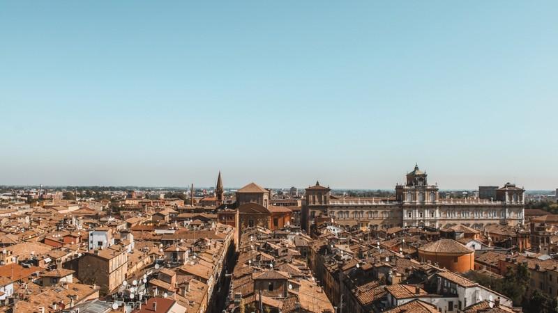 Una vista completa su tutta la città di Modena dall'alto della Ghirlandina. Spicca sulla destra il sontuoso Palazzo Ducale e al centro una chiesa a forma elicoidale con dietro il suo alto campanile a punta.