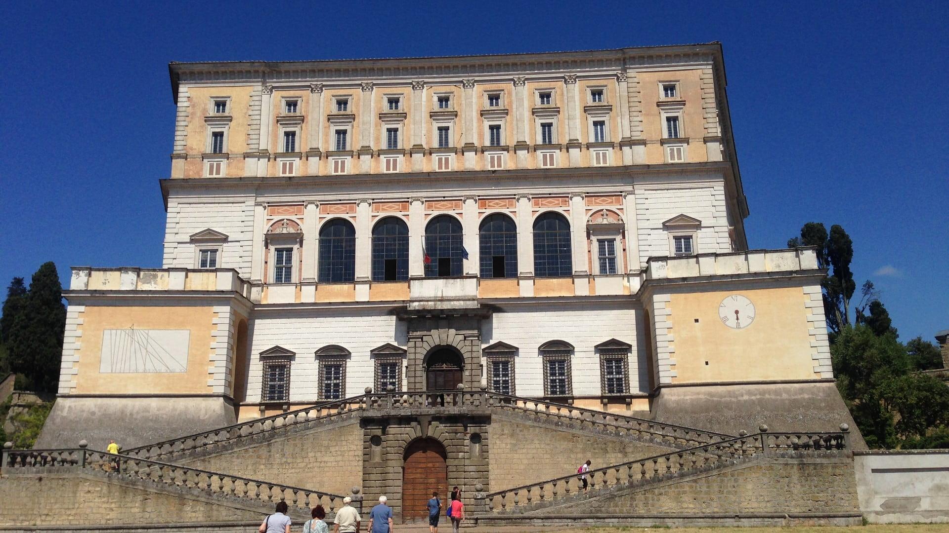 L'imponente Palazzo Farnese a Caprarola di cui spiccano la meridiana sulla sinistra e la grande scalinata a due rampe che accompagna al portone d'ingresso della struttura.