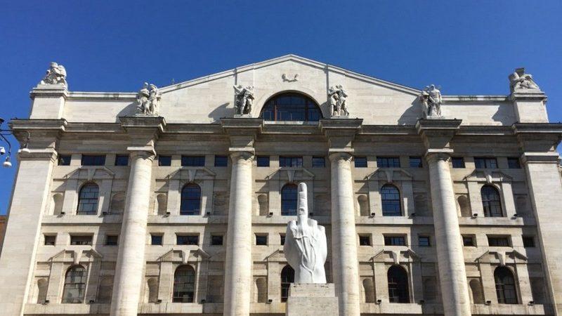 Piazza Affari di Milano è sicuramente una delle cose da vedere a Milano in un giorno. In primo piano la statua col dito medio alzato in mezzo alla piazza, sullo sfondo invece il palazzo con sei alti colonnati.