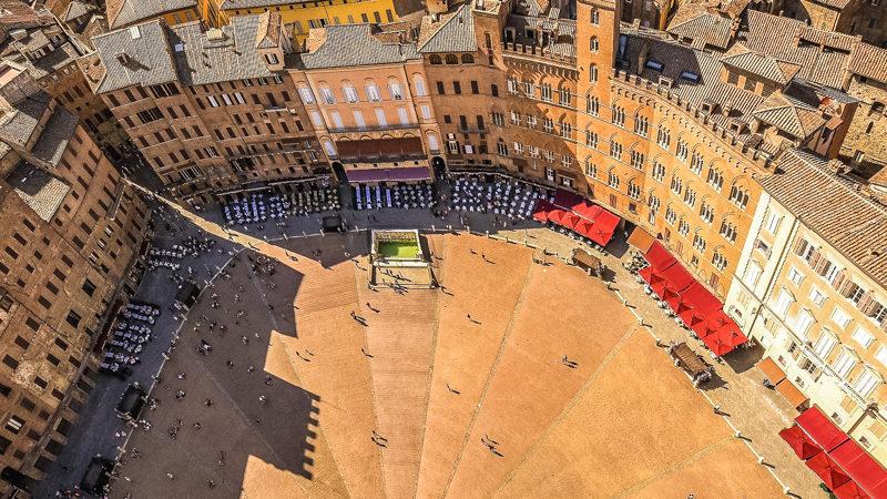 La meravigliosa piazza del campo di siena con la sua forma ellittica e i vari edifici o palazzi che la compongono. Al centro la vasca d'acqua con la fontana.