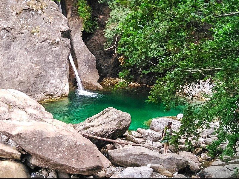 Una piccola cascatella che sbuca nel mezzo tra due grandissimi massi e che sfocia in una polla azzurra d'acqua. In primo piano i sassi che formano il contorno della polla d'acqua e un albero verde.
