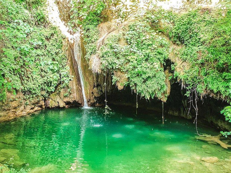 Una polla d'acqua limpidissima nel mezzo della natura rigogliosa della riserva naturale. Sullo sfondo una cascatella e alla sua destra una piccola grotta formata dalla natura verde.