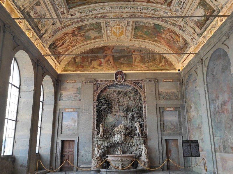 Il grandissimo salone d'ingresso del Palazzo Farnese a Caprarola con i tanti affreschi che abbelliscono il soffitto. A sinistra grandi finestre fanno penetrare la luce all'interno, mentre al centro una grande fontana.